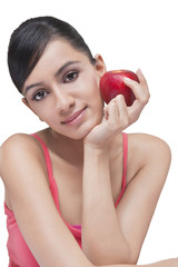 Portrait of beautiful woman with apple over white background