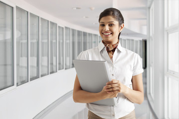Portrait of successful young businesswoman smiling with documents