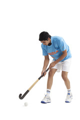 Young male Indian player practicing hockey isolated over white background