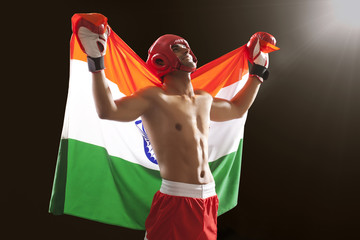 Happy male boxer looking up as he holds Indian flag isolated over black background