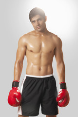 Portrait of shirtless young man wearing boxing gloves against white background