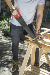 Carpenter holding a hand saw on the work bench