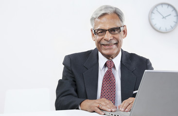 Old businessman with a laptop