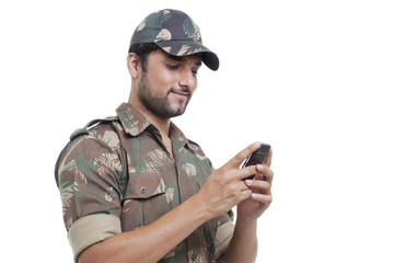 Smiling soldier texting on cell phone