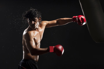 Handsome male boxer hitting heavy bag
