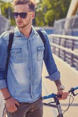 Stylish single speed cyclist on a bridge.