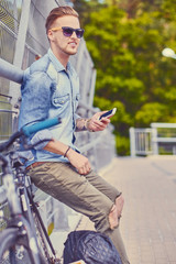 Cyclist using smartphone on a steel bridge.