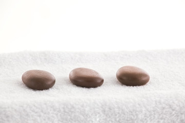 Massage stones in a row on a towel