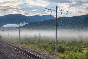 railway in the mountains, fog at dawn