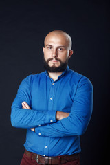 Portrait of a successful businessman on black background. Handsome bold man with beard