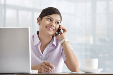 Happy young female executive using cell phone at her desk