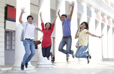 College students jumping with building in the background