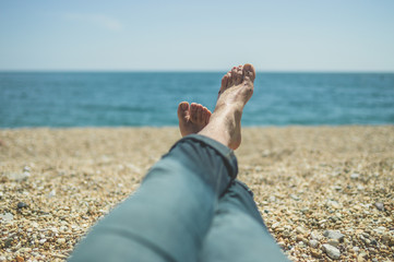 Feet of young man resting on beach
