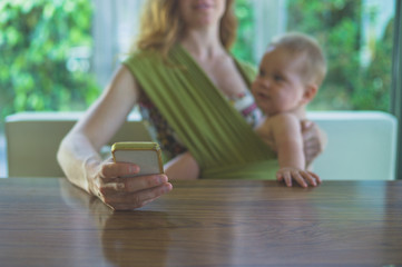 Mother with baby in sling using smartphone