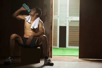Full length of tired young man drinking water from bottle at gym