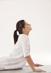 Woman in upward facing dog position over white background