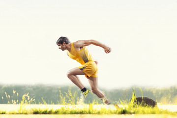 Profile shot of young male runner running outdoors