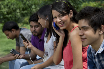 Group of young friends using cell phones