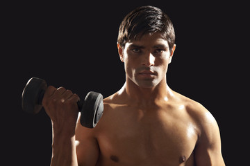 Portrait of young man exercising with dumbbell isolated over black background