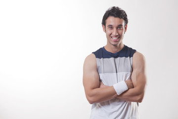 Portrait of a young fit man with arms crossed over white background