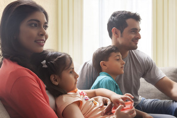 Family with son and daughter sitting on sofa and watching TV