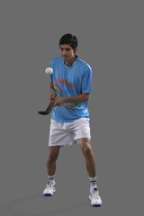 Full length of young Indian sportsman practicing hockey isolated over gray background