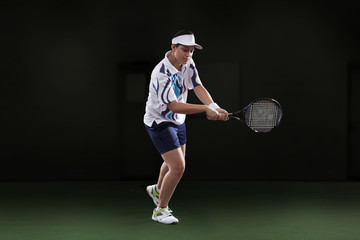 Young woman in sportswear playing tennis isolated over black background