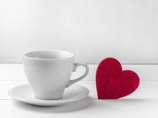 valentine day decoration with white cup of coffee and heart shape on wooden mock up over blurred green garden on day noon light,Image for Happy Valentine holiday concept.