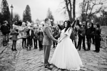 Gorgeous wedding couple holding hands on the pavement while crowd of kids takes pictures of them. Black and white photo.