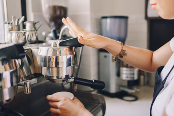Closeup of young Caucasian barista hands holding paper cup making coffee using  coffee machine. Woman pouring coffee from professional espresso machine. Toned with film filters.