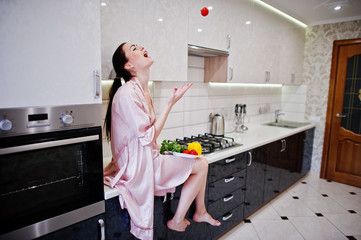 Portrait of a beautiful young woman in pink robe posing with a tomato in her kitchen.