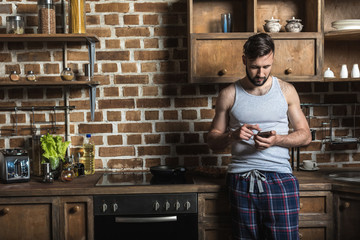 handsome bearded man in pajamas using smartphone while standing in kitchen