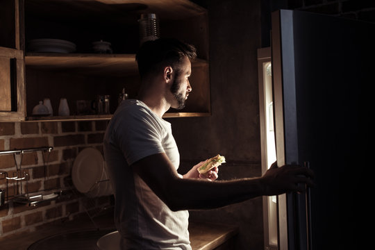 side view of bearded young man in pajamas eating and looking at refrigerator at night