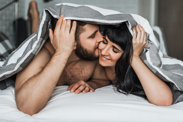 Loving couple in bed having sex. Guy and girl kissing in bed. Wedding night. Make love. Lovers in bed. The relationship between a man and a woman. Sex between a man and a woman. Hugs in bed.