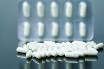 white medical drug on black background and reflection