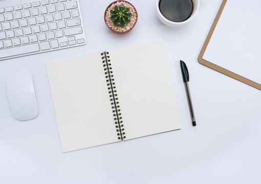 White office desk with notebook, pen, cactus, cup of coffee, mouse, computer. Top view and copy space for mockup, website banner, background, presentation and marketing material.