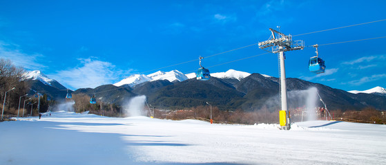 Bansko, Bulgaria ski resort panorama with pine trees, white snow peaks of the mountains, ski slope and snow canons