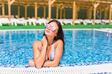 Beautiful woman relaxing in the swimming pool. Summer vocation.