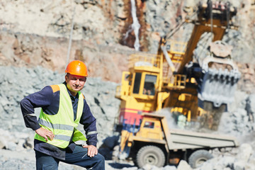 Worker of granite opencast. excavator loading dump truck