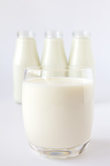 Bottle of milk and glass of milk on a white background