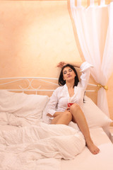 Frau mit Tasse entspannt im Himmelbett