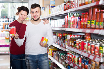 cheerful couple choosing purchasing canned food for week at supermarket
