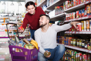 Family purchasing tinned goods at grocery store