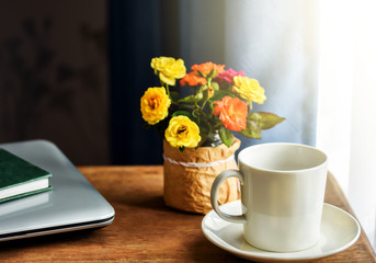 White coffee cup on wooden working desk by the window . Laptop and green notebook placed beside ready to work at home. Colorful small roses vase as background.