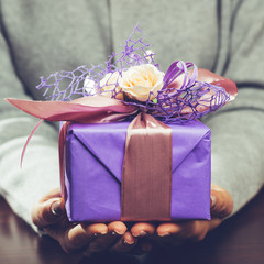 woman received beautiful purple gift box with present. For Mothers Day, Valentines Day and Birthdays, toned image