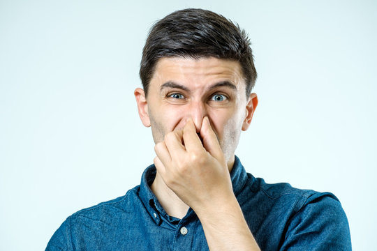 Man holding his nose against a bad smell over gray background