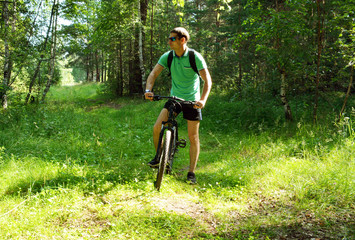 Biker with a mountain bike in the forest in summer