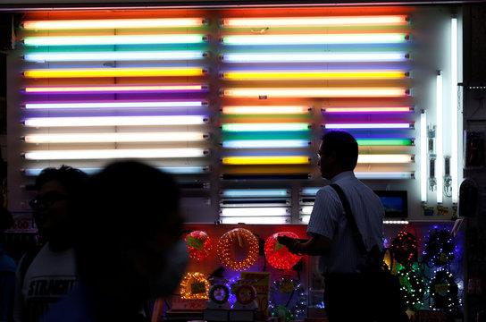 Pedestrians walk near fluorescent light tubes displayed outside a light bulb store in Tokyo's Akihabara district