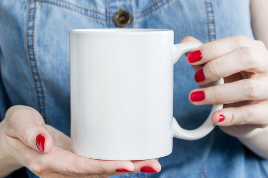 Girl is holding white mug, cup in hands. Mock-up for products presentations.