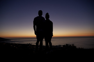 Couple standing by the sea at sunset on a beach, silhouette